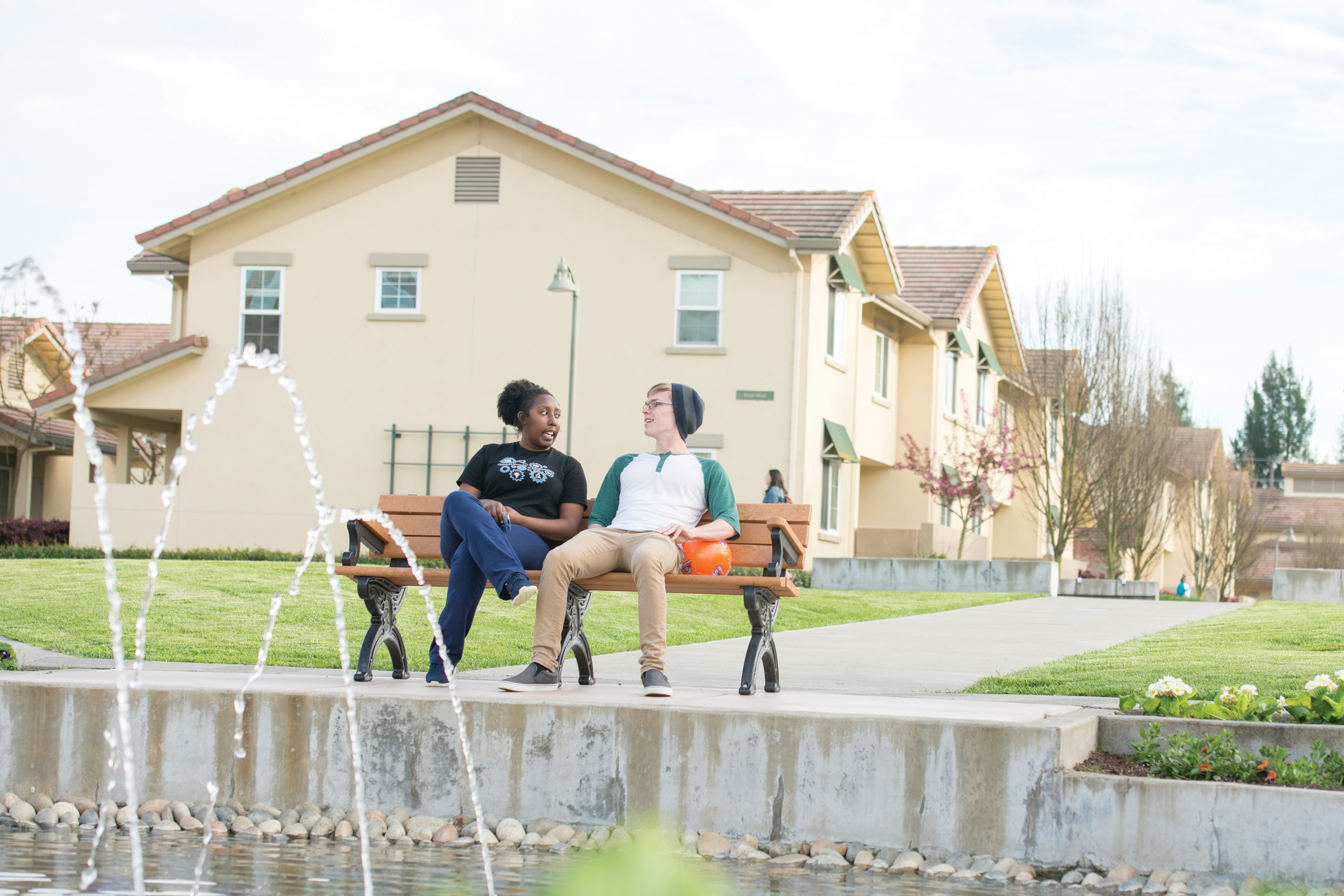 Two students seated on a bench next to a fountain with residence halls in the background