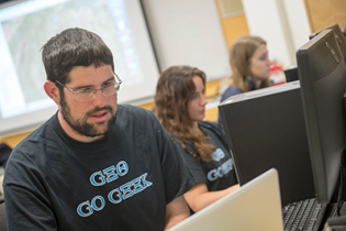 Male student at computer with Geo Go Geek t-shirt