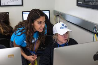 Two students wearing Sonoma State University branded clothing looking at a computer screen